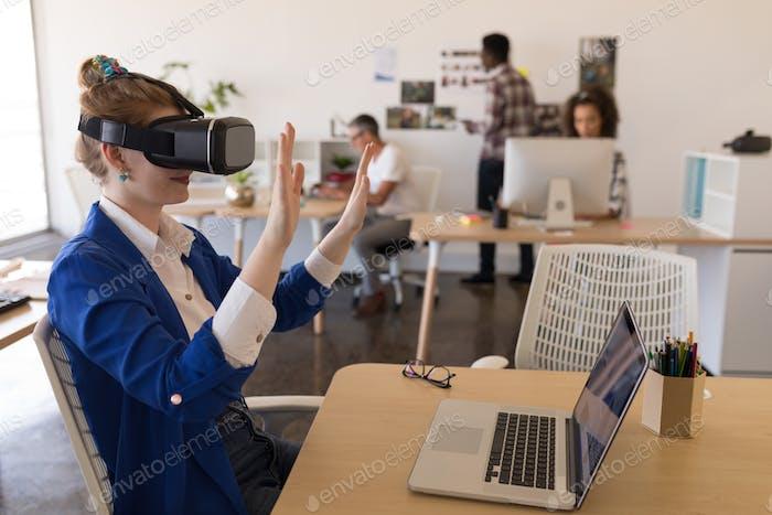 Seitenansicht der jungen kaukasischen Geschäftsfrau mit Virtual Reality Headset am Schreibtisch im modernen Büro