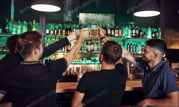 Amis reposant dans le pub avec de la bière dans les mains. Avoir une conversation