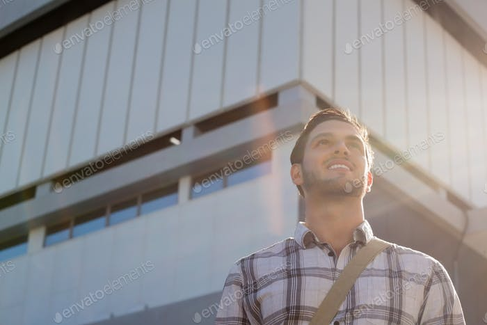 Low angle view of smiling man looking away