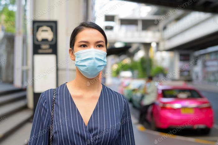 Young Asian businesswoman with mask waiting at the taxi station in the city streets