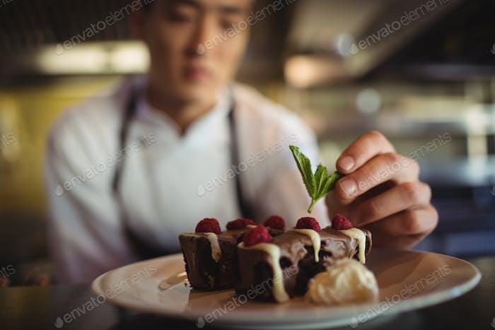 Male chef garnishing dessert plate