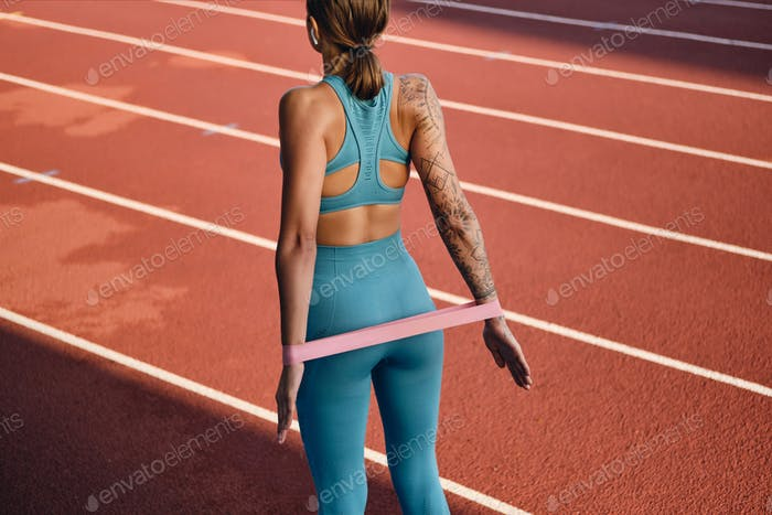 Sporty girl in stylish sportswear stretching with rubber band during workout on city stadium