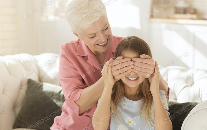 Playing Guess Who game. Cheerful elderly lady covering her granddaughter's eyes, making surprise
