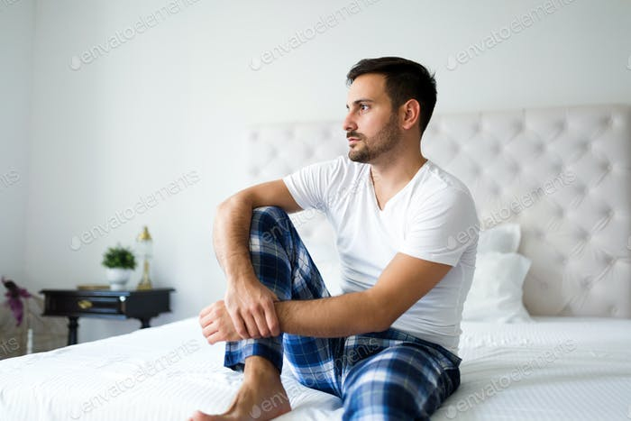 Portrait of unhappy man sitting on bed