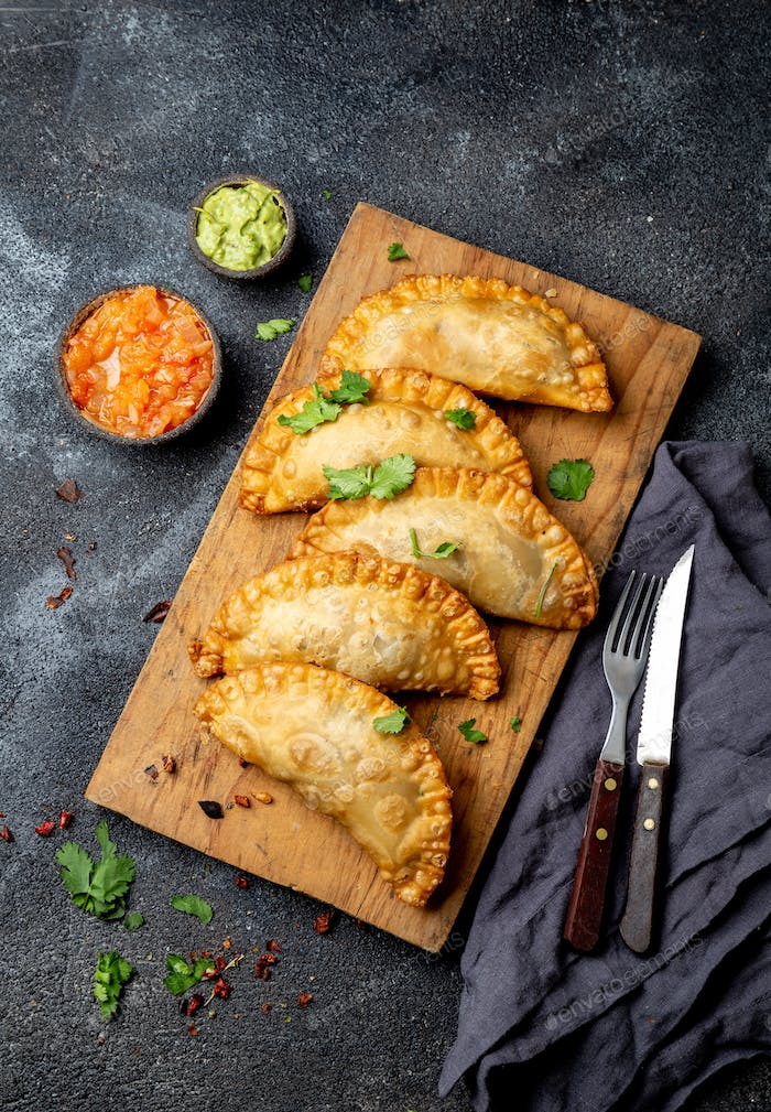 Latin American fried empanadas with tomato and avocado sauces. Top view