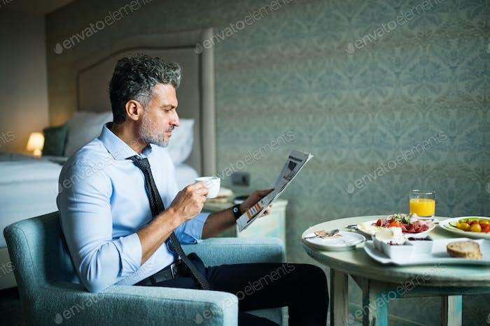 Mature businessman having breakfast in a hotel room.