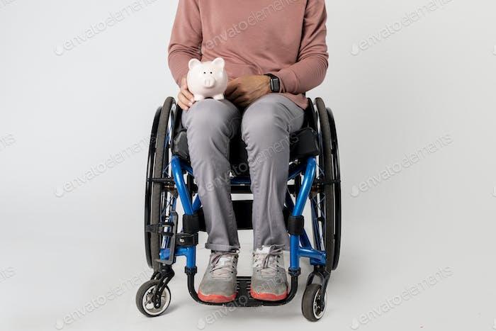 Mujer en una silla de ruedas con una alcancía