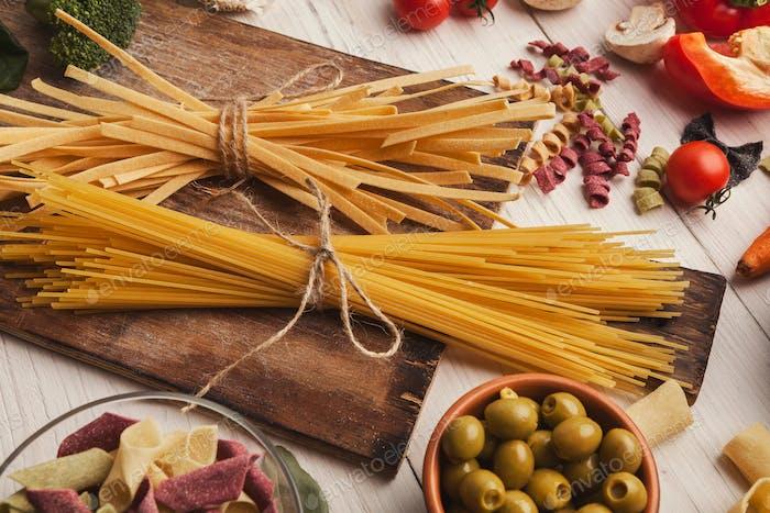 Pasta und Kochzutaten auf weißem Holz