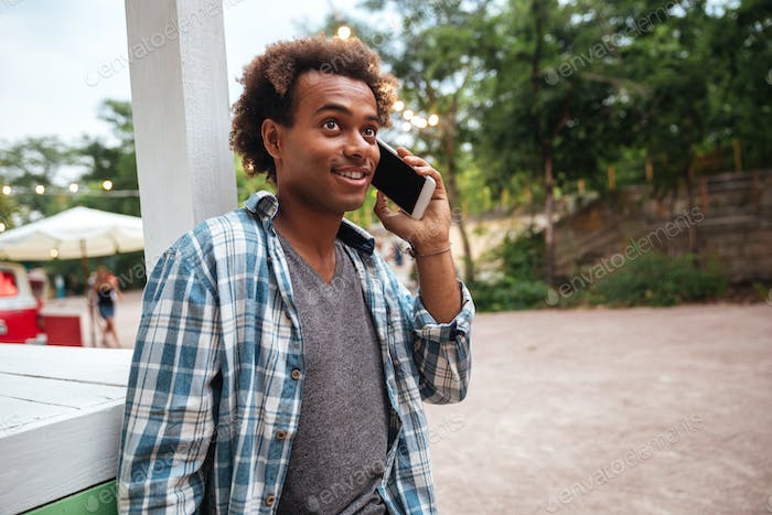 Cheerful african man talking on cell phone