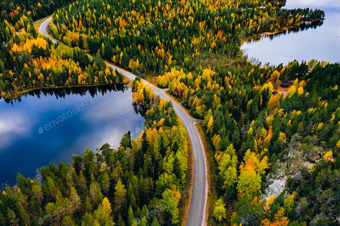 Aerial view of road and colorful autumn  forest with mountains and blue lakes in Finland.