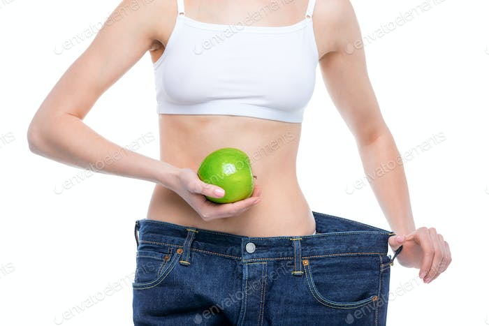 Mid section of young slim woman in oversized jeans holding green apple  isolated on white