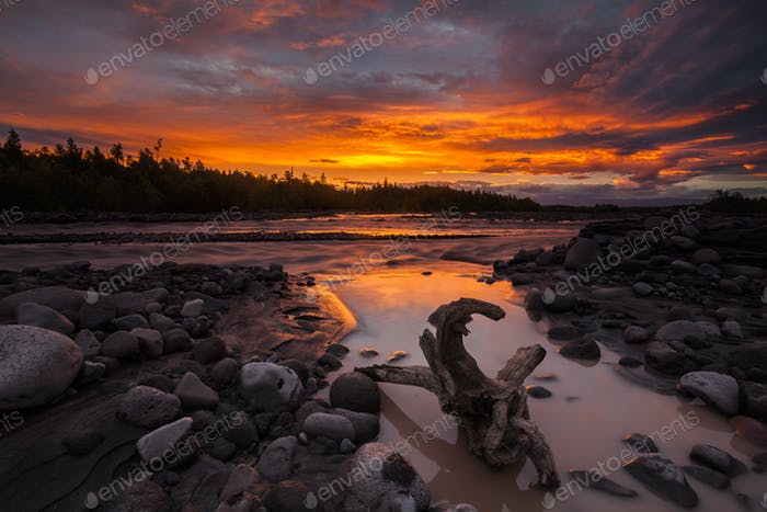 Magic fiery sunset over a beautiful lake with a rocky shore
