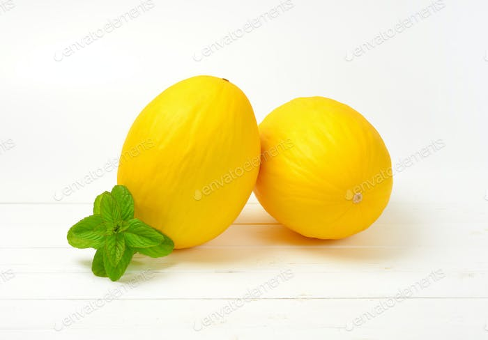 two whole yellow melons on white wooden background