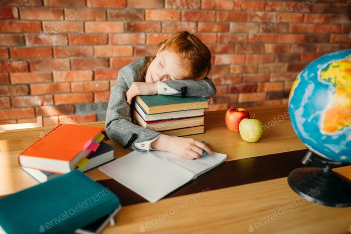 Tired female pupil asleep on stack of textbooks