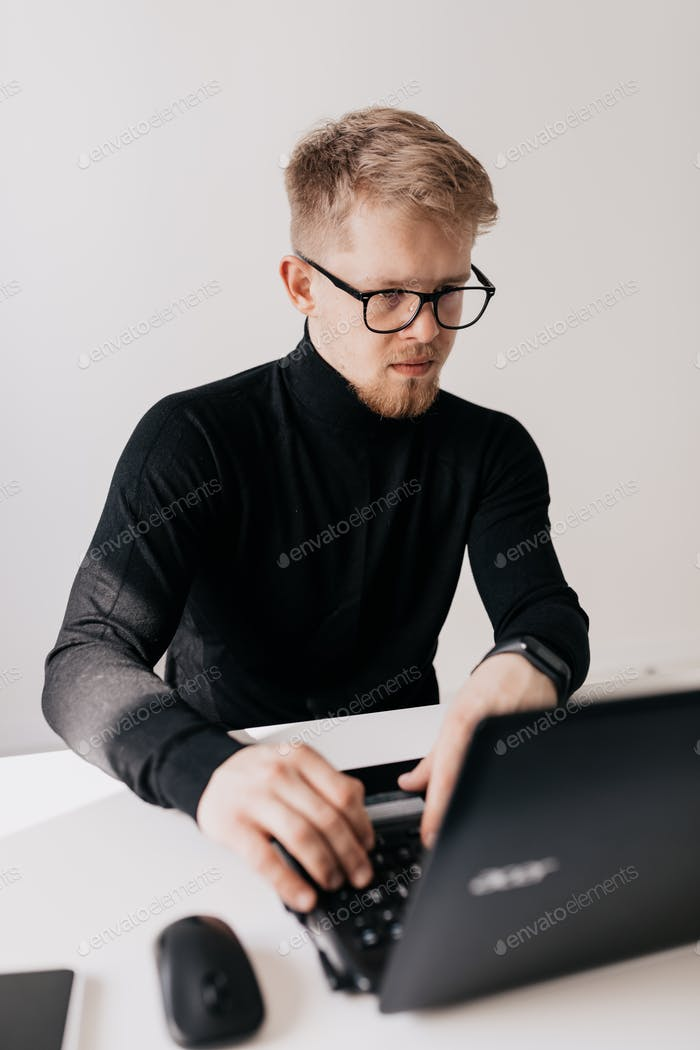 Confident stylish man working on laptop modern light office in sunny good day