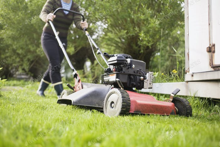 Low section of woman mowing lawn