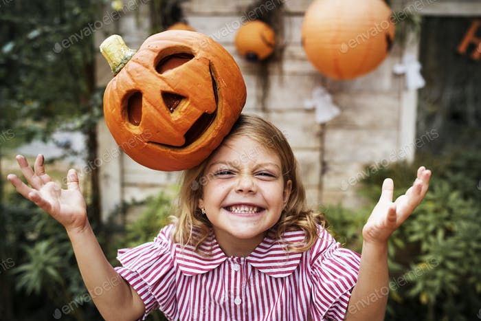 Young playful girl with her Halloween jack-o'-lantern