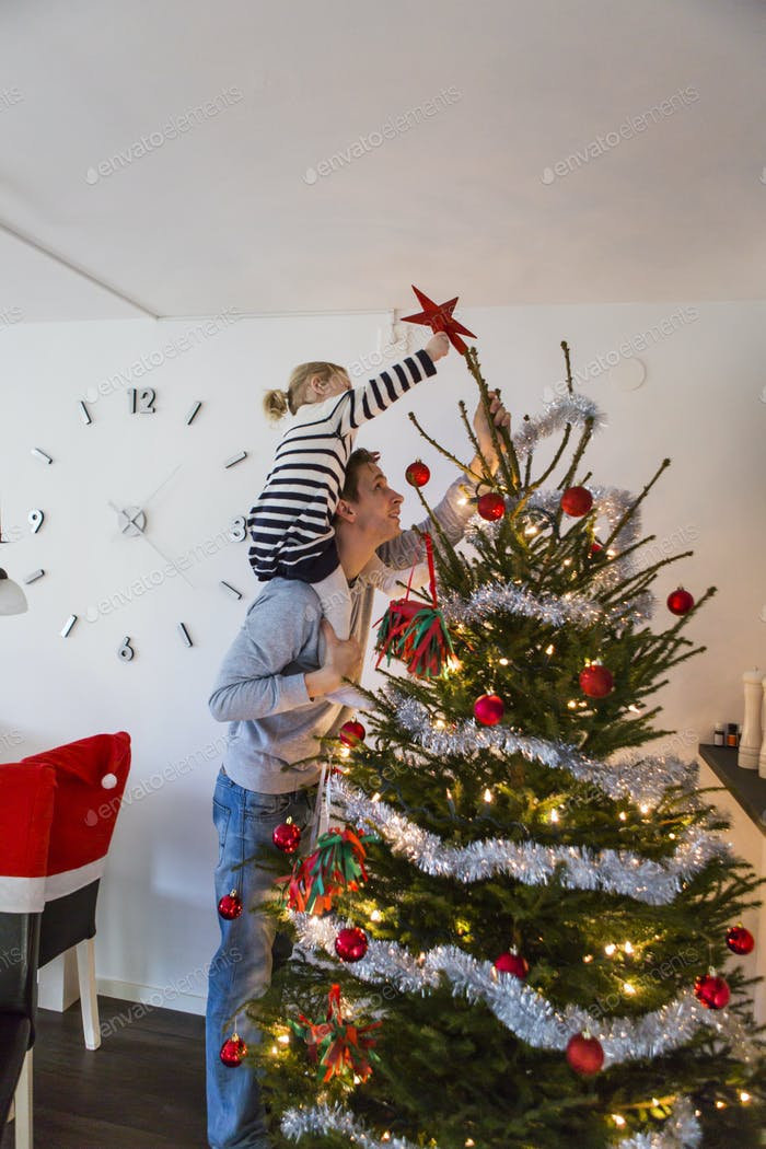 Father and daughter decorating Christmas tree at home