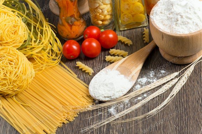 Nudeln, Tomaten und Mehl auf dem Löffel