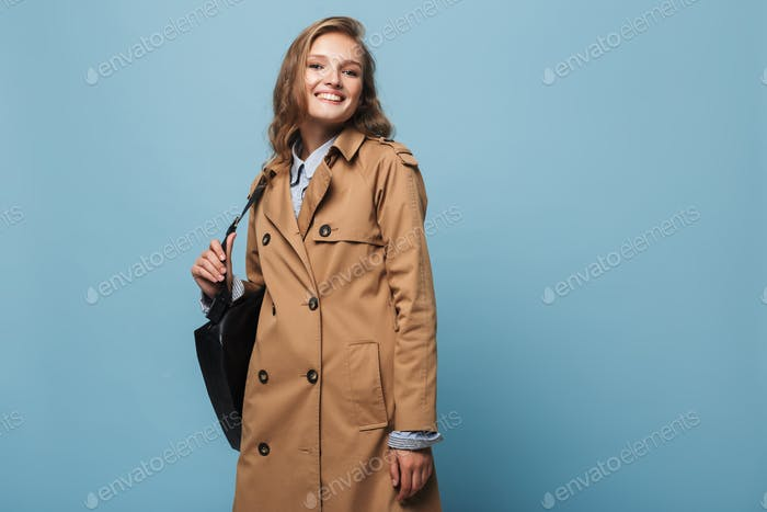 Beautiful smiling girl with wavy hair in trench coat with black backpack happily looking in camera
