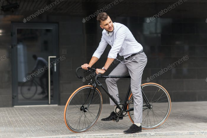 man with bicycle and headphones on city street