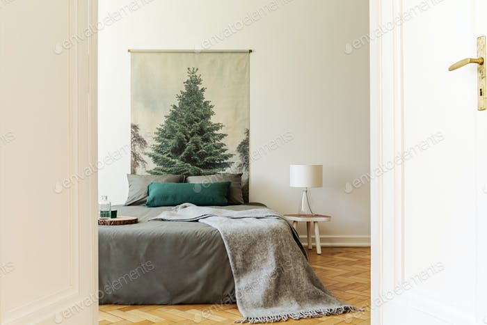 A peek through an open door into a simple style bedroom interior