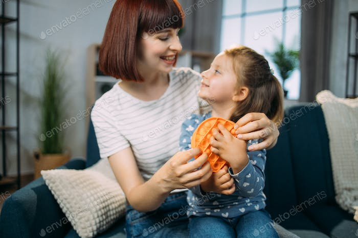 Mother and her adorable little daughter playing with round silicone colorful anti stress pop it toy