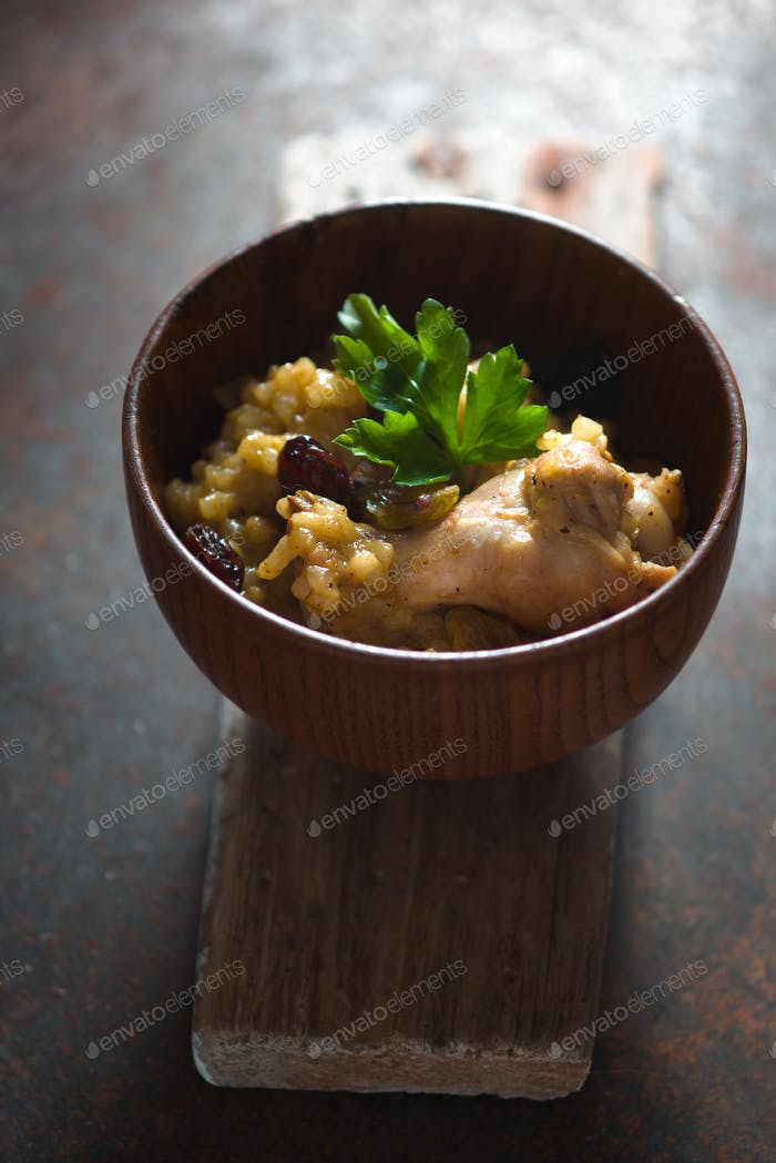 Pilaf with rice, chicken and raisins in a wooden bowl