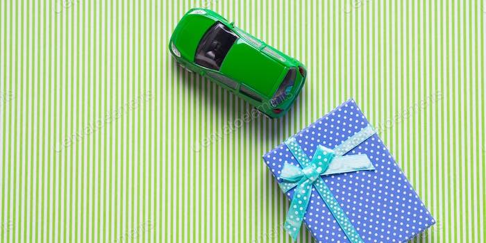 Голубая подарочная коробка и игрушечный автомобиль