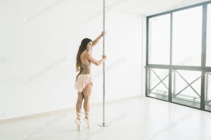 Flexible lady posing near pole in studio