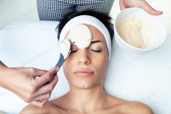 Cosmetologist applying the alginates facial mask to woman on the spa center.