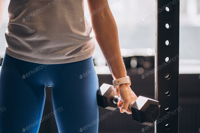 Slender athletic girl performs physical exercises with dumbbells