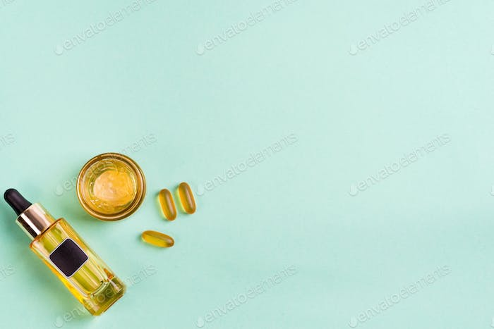 Beauty natural products with cosmetic cream, Omega-3 gel capsules, and oil in glass bottles on blue