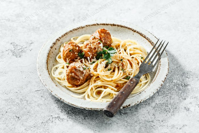 Homemade spaghetti and meatballs served with fresh herbs and parmesan cheese