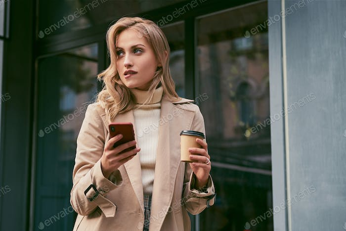 Flirty blond girl in trench coat with coffee to go and cellphone dreamily looking away outdoor