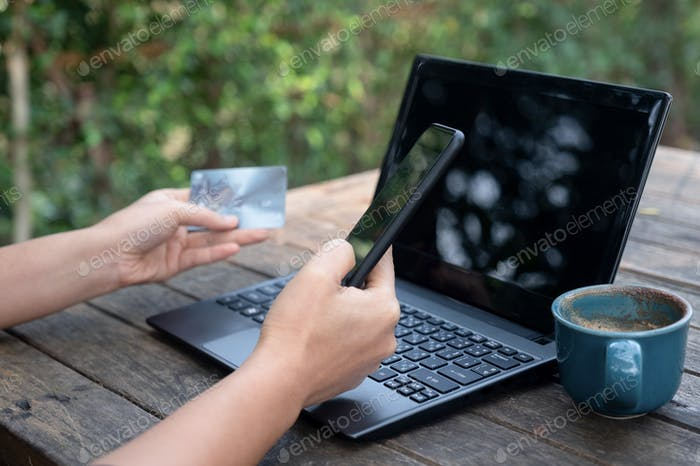 Smartphone and credit cards in hand with laptop and coffee.