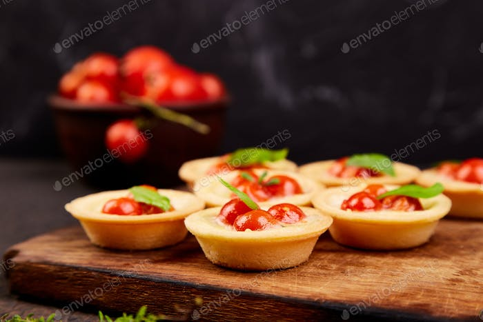 Mini tarts with cherry tomatoes with mozzarella cheese