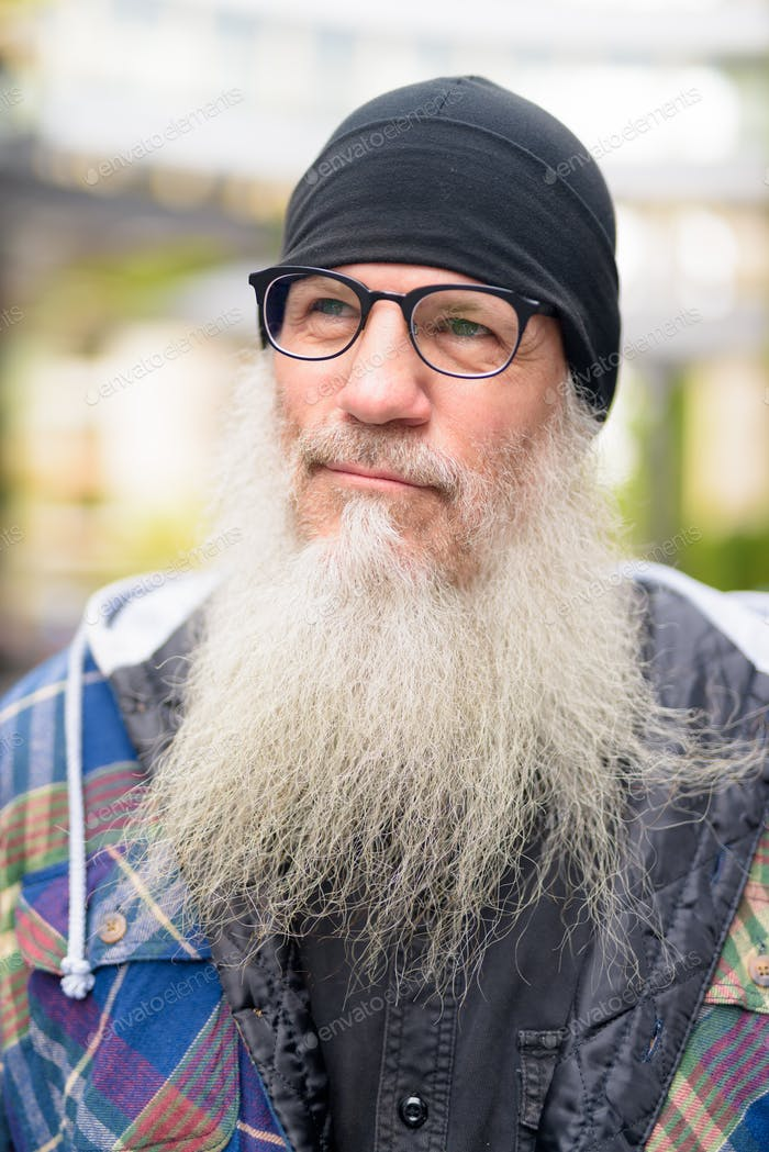 Face of mature bearded hipster man with eyeglasses thinking outdoors