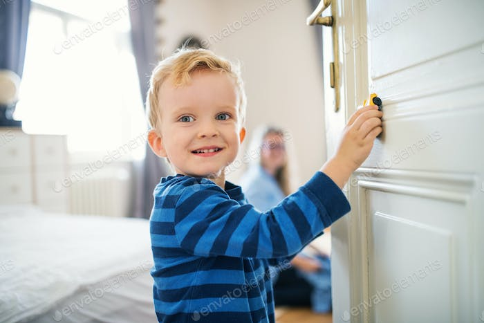 A toddler boy standing by the door inside in a bedroom, playing with car.
