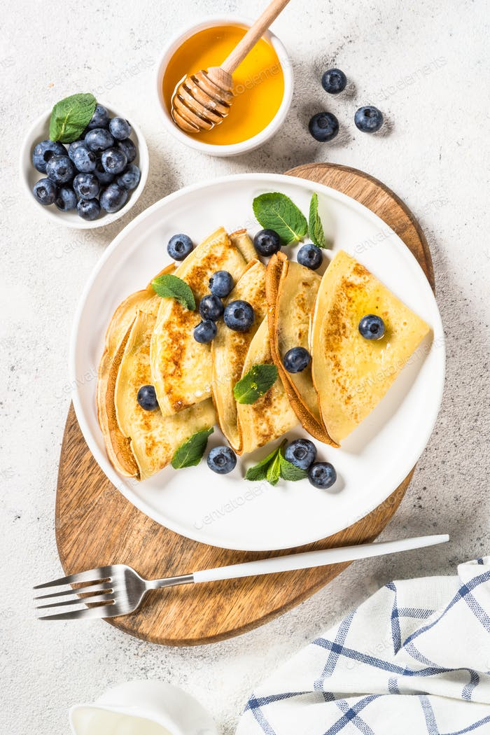 Crepes with blueberries at white table