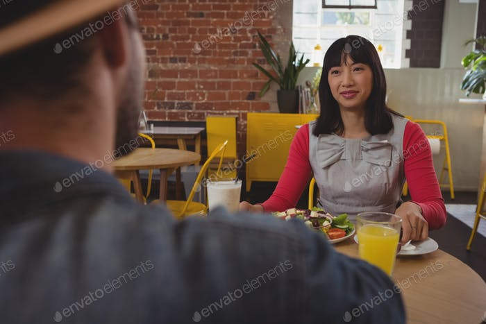 Young woman looking at man in cafe