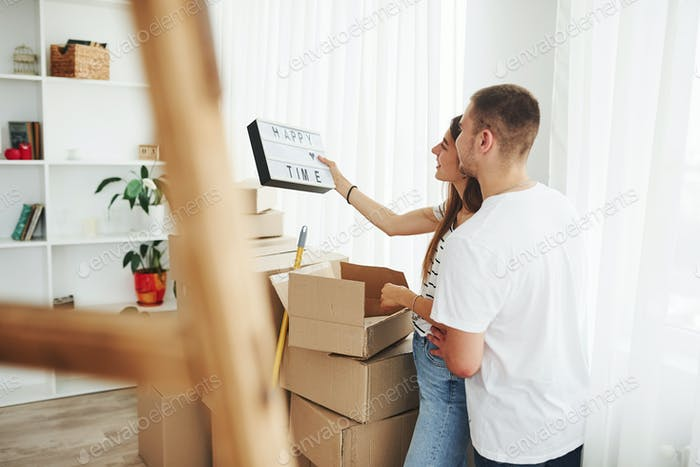 Cheerful young couple in their new apartment. Conception of moving