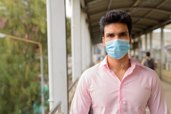 Young Indian businessman wearing mask for protection from corona virus outbreak at the footbridge