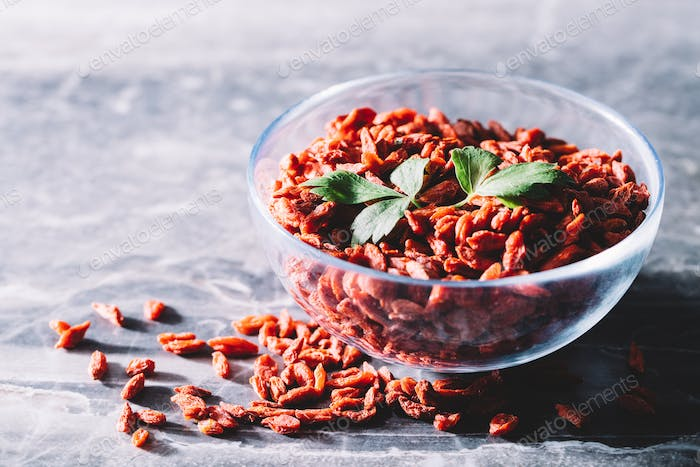 Goji berries and green leaves in a glass bowl