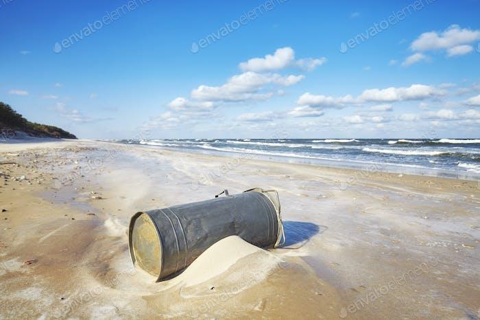 Trash can on a beach, environmental pollution concept