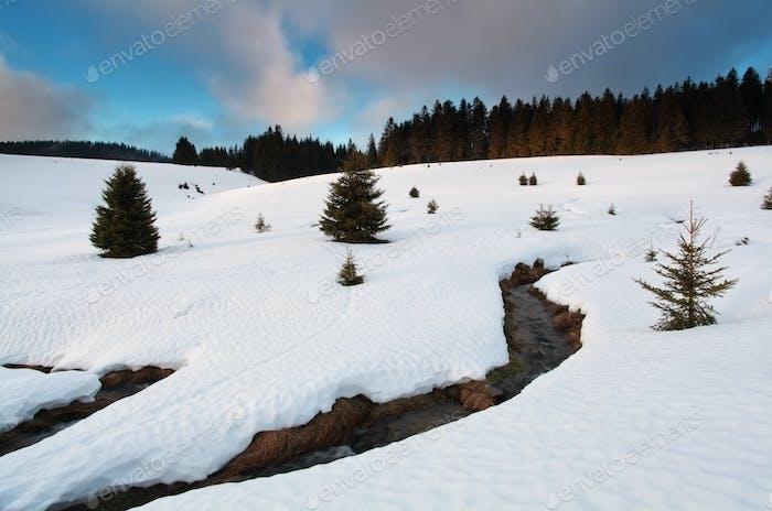 Gebirgsfluss zwischen verschneiten Hügeln