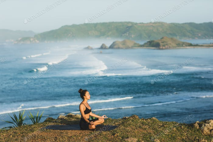 Woman practicing yoga and sitting in lotus pose outdoor with amazing view. Health and wellbeing