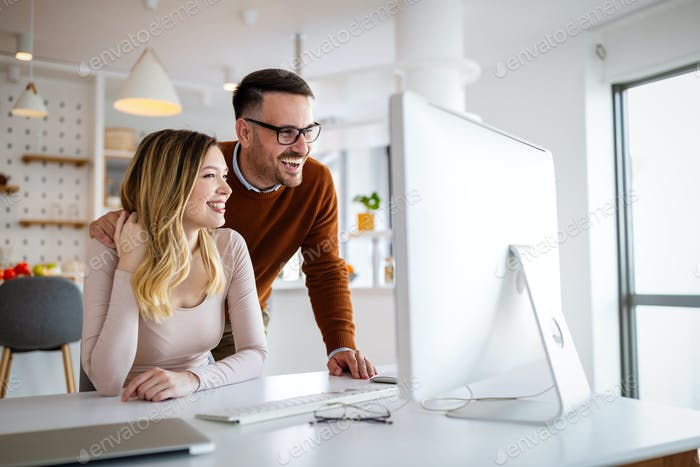 Happy couple in love working together on computer