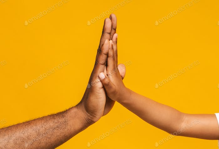 High five gesture of african father and child