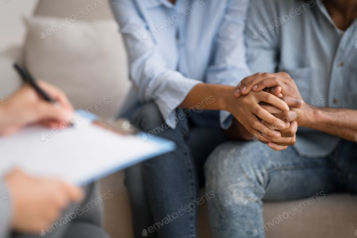 Black Husband And Wife Holding Hands At Marital Psychologist's Office